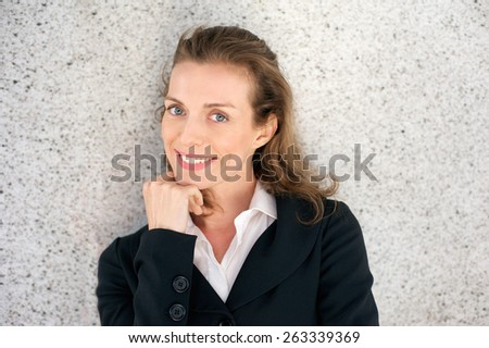 Close up portrait of an attractive business woman smiling with hand on chin - stock photo