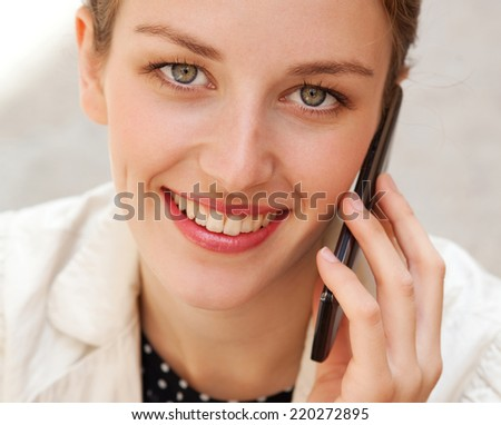 Close up portrait of an attractive business woman using a smartphone having phone call conversation in a city street, smiling outdoors. Professional people and technology.