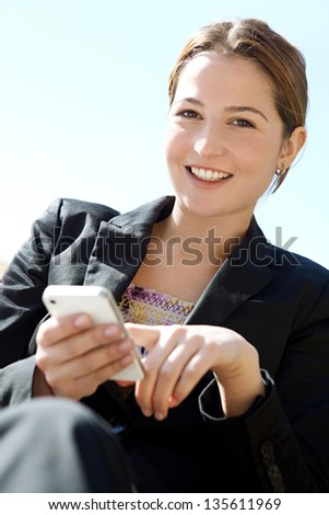 Close up portrait of an attractive business woman using a smartphone while sitting dow against a blue sky, smiling. - stock photo