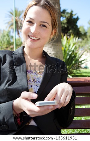 Close up portrait of an attractive business woman using a smartphone while sitting down in a park bench, smiling. - stock photo