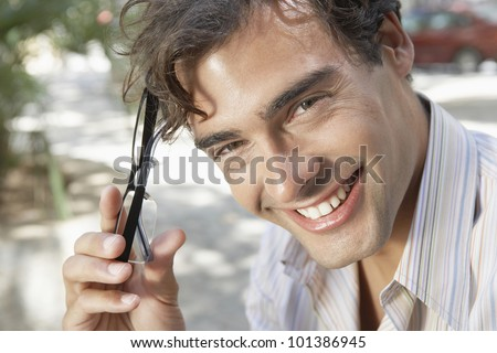 Close up portrait of an attractive businessman holding his spectacles and smiling to camera, outdoors. - stock photo