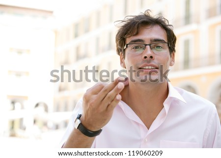 Close up portrait of an attractive businessman using his hands to express himself while standing next to office buildings in a classic city square. - stock photo