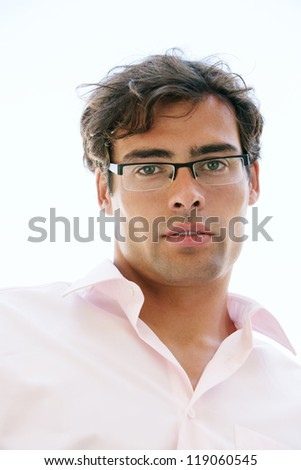 Close up portrait of an attractive businessman wearing glasses and looking at the camera against a blue sky background. - stock photo