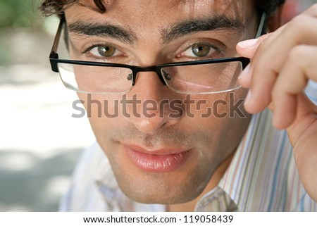 Close up portrait of an attractive businessman wearing glasses and looking at the camera in the city, outdoors. - stock photo