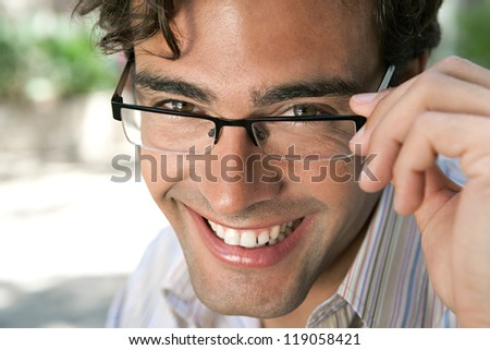 Close up portrait of an attractive businessman wearing glasses and looking at the camera smiling, outdoors. - stock photo