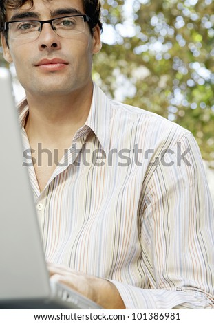 Close up portrait of an attractive businessman wearing glasses and using a laptop computer in the park. - stock photo