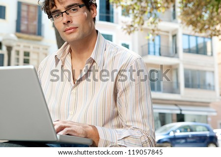Close up portrait of an attractive businessman wearing glasses and using a laptop computer in the city, outdoors. - stock photo