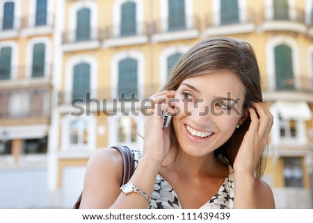 Close up portrait of an attractive businesswoman having a conversation on her cell phone outdoors, smiling.
