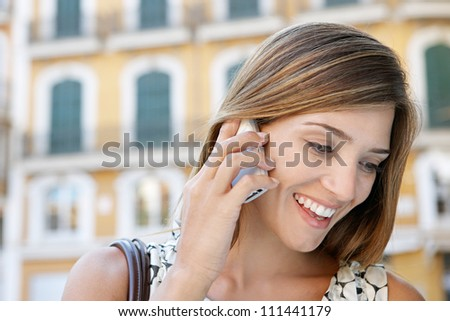 Close up portrait of an attractive businesswoman having a conversation on her cell phone outdoors, smiling. - stock photo