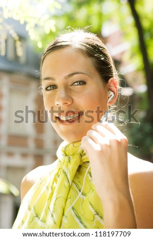 Close up portrait of an attractive businesswoman using a hands free cell phone device to have a professional conversation while standing in a classic city financial district, smiling. - stock photo