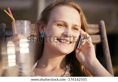Close up portrait of an attractive happy young woman relaxing in a deckchair in the sun talking on her smart phone and smiling while drinking coffee cocktail with a straw in the beach cafe - stock photo