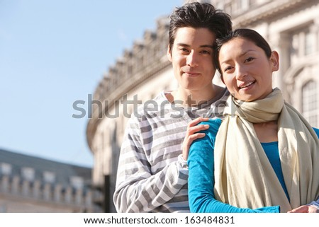 Close up portrait of an attractive Japanese tourist couple visiting the city of London during a sunny day and standing on Regents Street landmark while smiling and holding each other, outdoors.