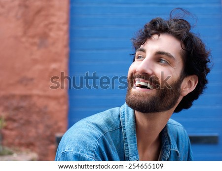Close up portrait of an attractive man with beard laughing  - stock photo