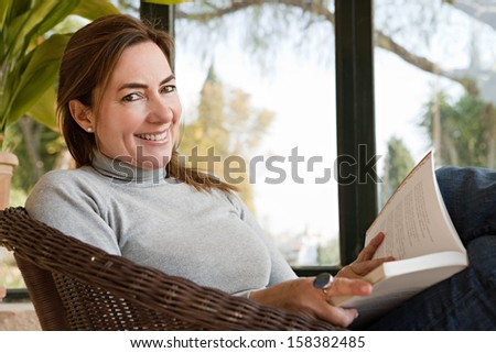 Close up portrait of an attractive mature woman sitting at howe by large glass windows and a green garden, reading a book and relaxing indoors, smiling during a sunny day.