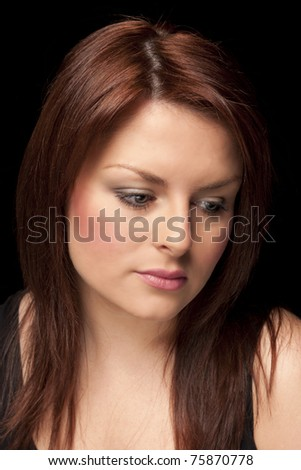 Close-up portrait of an attractive model looking sad isolated on black