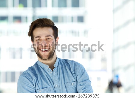 Close up portrait of an attractive modern young man with beard smiling - stock photo