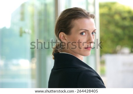 Close up portrait of an attractive profession business woman standing outside in black jacket - stock photo