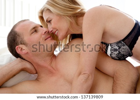Close up portrait of an attractive sexy couple being intimate and kissing while laying down on a white bed in a home bedroom.