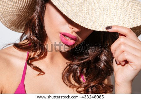 Close-up portrait of an attractive sexy woman in beach hat isolated on the white background - stock photo