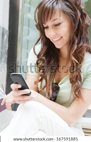 Close up portrait of an attractive teenager woman networking and using her smartphone while sitting and taking a break by a store display window during a shopping day out, outdoors. - stock photo