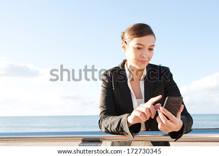 Close up portrait of an attractive young business woman leaning on a silver banister using a smartphone mobile phone during a sunny day, outdoors against a bright blue sky, smiling. - stock photo
