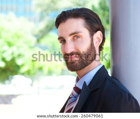Close up portrait of an attractive young businessman standing outdoors in suit - stock photo