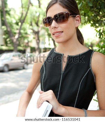 Close up portrait of an attractive young businesswoman holding a laptop computer under her arm and wearing shades while in a leafy street in the city with classic architecture.