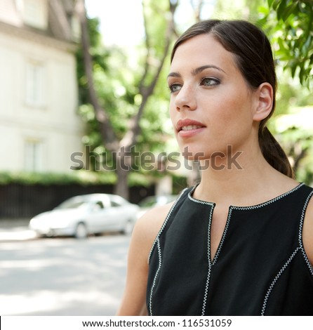Close up portrait of an attractive young businesswoman smiling in a leafy street in the city with classic architecture. - stock photo