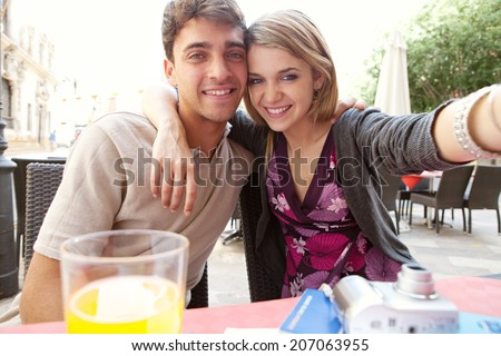 Close up portrait of an attractive young couple on holiday, taking selfies self photos with a smartphone camera during a sunny day on vacation. Love and technology lifestyle, outdoors. - stock photo