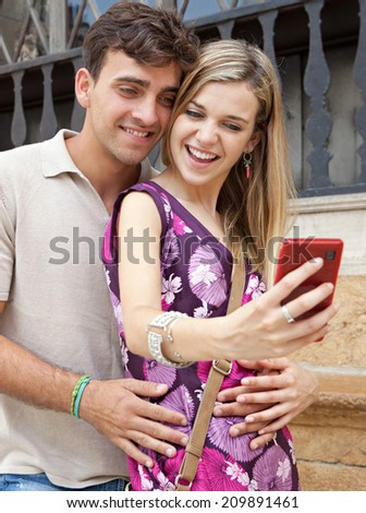 Close up portrait of an attractive young couple relaxing and taking a selfie picture of themselves with a smartphone visiting a destination city on holiday, together outdoors. Technology lifestyle. - stock photo