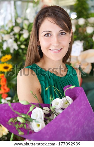 Close up portrait of an attractive young customer woman buying and holding a bouquet of fresh flowers while visiting a florist market stall in a city street. Outdoors lifestyle shopping. - stock photo