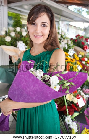 Close up portrait of an attractive young customer woman buying and holding a bouquet of fresh flowers while visiting a florist market stall in a city street. Outdoors lifestyle shopping.