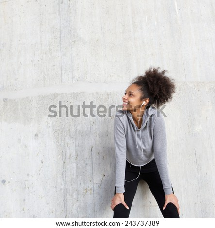 Close up portrait of an attractive young fitness woman smiling with earphones - stock photo