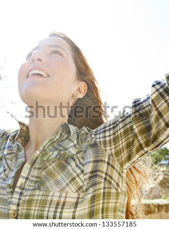 Close up portrait of an attractive young woman enjoying the sun with her arms outstretched and her head leaning back, smiling.