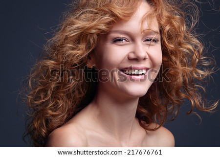 Close up portrait of an attractive young woman laughing with hair blowing - stock photo