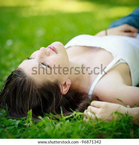 Close-up portrait of an attractive young woman outdoors, lying in the grass, relaxing - stock photo