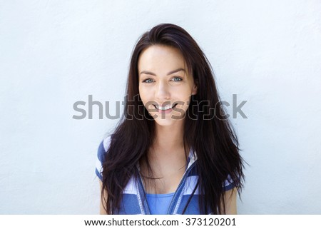 Close up portrait of an attractive young woman smiling against a white wall - stock photo