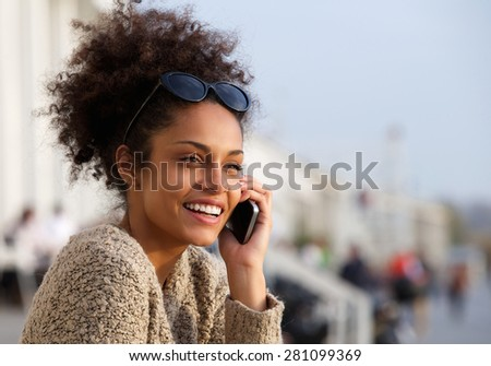 Close up portrait of an attractive young woman smiling and talking on mobile phone - stock photo