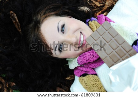 Close-up portrait of an beautiful autumn woman laying on fall leafs  and eating chocolate - stock photo