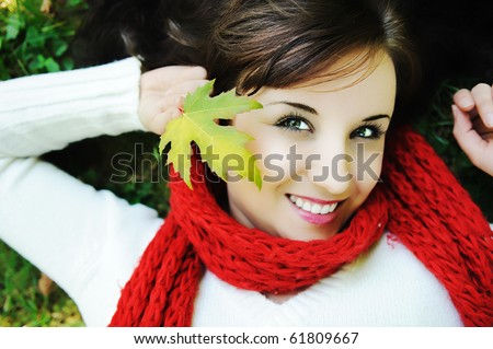 Close-up portrait of an beautiful autumn woman laying on ground with leave in hand - stock photo