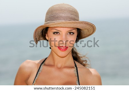 Close up portrait of an beautiful woman smiling with a sun hat on a tropical beach