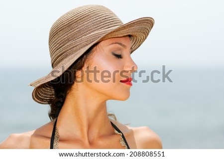 Close up portrait of an beautiful woman wearing sun hat on a tropical beach with her eyes closed