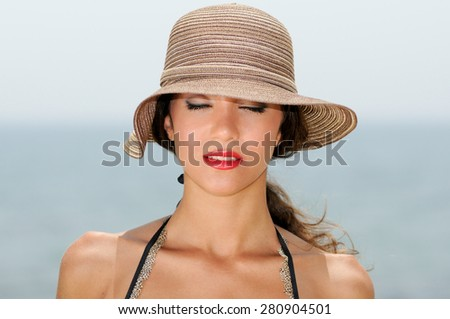 Close up portrait of an beautiful woman wearing sun hat on a tropical beach with her eyes closed - stock photo