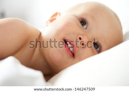 Close up portrait of an cute baby lying in bed