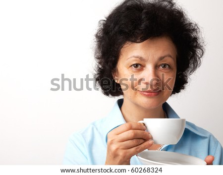 Close-up portrait of an elder smiling woman holding cup and saucer. - stock photo