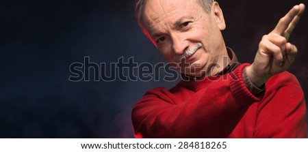 Close-up portrait of an elderly man gesturing at a blurred background - stock photo