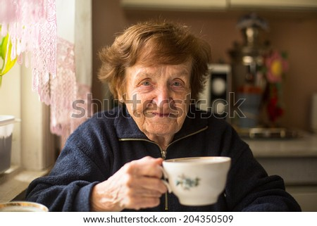 Close-up portrait of an elderly woman drinking tea at her home. - stock photo