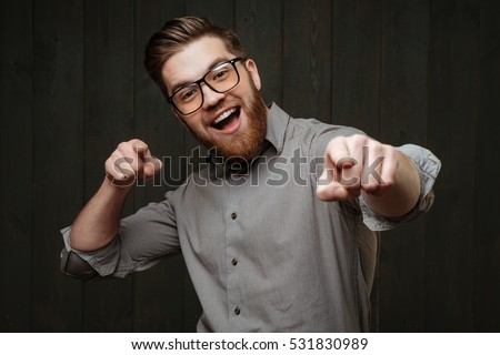 Close up portrait of an excited happy man in eyeglasses pointing fingers at camera isolated on the black wooden background