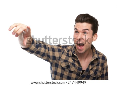 Close up portrait of an excited young man pointing finger on isolated white background - stock photo