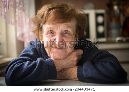 Close-up portrait of an happy old woman - stock photo